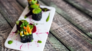 Raw vegan sushi rolls with vegetables and green sauce with food styling in restaurant ** Note: Visible grain at 100%, best at smaller sizes