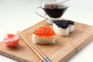 Two heart shaped sushi with salmon roe and beluga caviar on wooden desk. ginger, chopsticks and soy sauce.